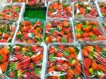 algumas caixas plásticas completas das morangos vermelhas envolvidas com plástico transparente em uma prateleira verde no mercado fotos de stock