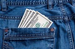 Algumas contas de cem dólares colam fora do bolso traseiro das calças de brim fotografia de stock