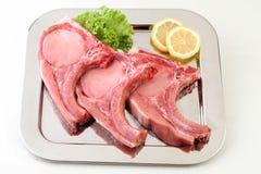 Algumas costeletas de carne de porco frescas na placa preta Imagens de Stock