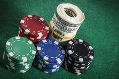 Algumas microplaquetas de pôquer na tabela verde Fotos de Stock