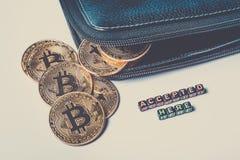 Algumas moedas de ouro com o sinal do bitcoin caíram fora da bolsa e do ` aqui aceitado ` da inscrição Imagem tonificada imagens de stock royalty free