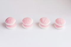 Algumas partes de doces e de geleia cor-de-rosa e brancos estão em um CCB branco Fotografia de Stock Royalty Free