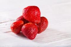 Algunas bayas rojas de la fresa en los tableros blancos Imagenes de archivo