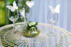 Algunas copas de vino adornadas con las mariposas Imagen de archivo