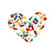 Algunas diversas píldoras en una forma del corazón Imagen de archivo