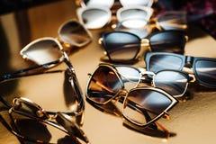 Algunas gafas de sol de la élite en un marco de moda moderno en un fondo del oro imagen de archivo