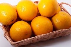 Algunas naranjas en una cesta en fondo de madera fotografía de archivo