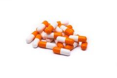 Algunas píldoras blanco-anaranjadas situadas   Imágenes de archivo libres de regalías