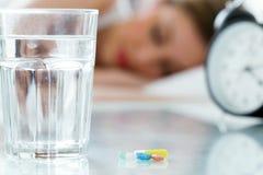 Algunas píldoras, un vidrio de agua y un reloj En el fondo, mujer bonita que duerme en cama Imágenes de archivo libres de regalías