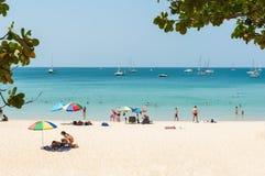 Algunas personas se relajan en la playa blanca de la arena Fotografía de archivo