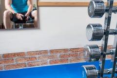 Algunas pesas de gimnasia de plata están en el primero plano y un espejo con la imagen de espejo de un atleta cuelga en la pared imagen de archivo libre de regalías