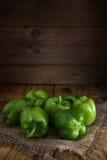 Algunas pimientas verdes frescas en la arpillera en una tabla de madera Imagenes de archivo