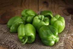 Algunas pimientas verdes frescas en la arpillera en una tabla de madera Fotografía de archivo libre de regalías