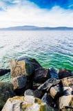 Algunas rocas delante del lago grande agradable foto de archivo