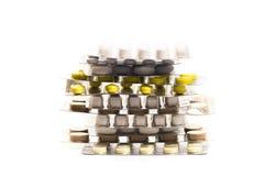 Algunas tabletas ampollan paquetes con las diversas píldoras y las cápsulas apiladas y en el fondo blanco foto de archivo