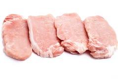 Algunas tajadas de cerdo frescas en la placa negra Imagen de archivo