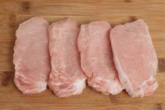 Algunas tajadas de cerdo frescas en la placa negra Fotografía de archivo libre de regalías