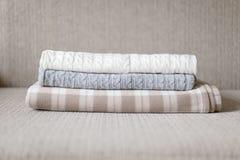 Algunas telas escocesas acogedoras en un sofá Concepto del otoño o del invierno Fotografía de archivo