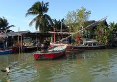 Algunos barcos de pesca tradicionales en frente de un pueblo Imagen de archivo
