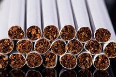 Algunos cigarrillos finos en cierre negro del fondo para arriba Foto de archivo libre de regalías