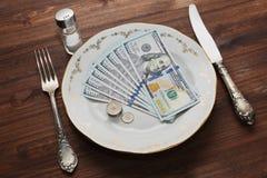 Algunos dólares de EE. UU. servered como una comida en la placa del vintage Imagen de archivo
