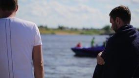 Algunos hombres jovenes activos se colocan delante del río y de la mirada en el barco de motor flotante almacen de metraje de vídeo