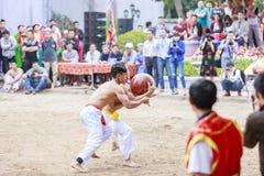 Algunos hombres jovenes juegan con la bola de madera en Año Nuevo lunar del festival en Hanoi, Vietnam el 27 de enero de 2016 Fotografía de archivo libre de regalías