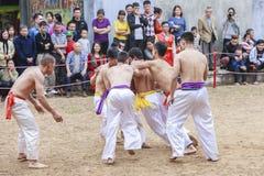 Algunos hombres jovenes juegan con la bola de madera en Año Nuevo lunar del festival en Hanoi, Vietnam el 27 de enero de 2016 Fotos de archivo libres de regalías
