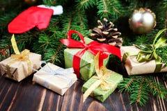 Algunos presentes agradables en un documento de embalaje del Año Nuevo sobre la tabla de madera, árbol de navidad hermoso en el f Imágenes de archivo libres de regalías