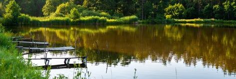 Algunos puentes o plataformas pesqueros en el lago más forrest en donde los árboles reflejan en agua, fondo panorámico imagen de archivo