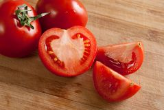 Algunos tomates rojos en la tarjeta de corte Imagen de archivo libre de regalías