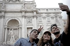 Algunos turistas toman una imagen en fuente del Trevi en Roma Imágenes de archivo libres de regalías