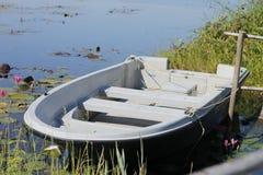 Alguns barcos de enfileiramento para o aluguer encontram-se na borda das águas Imagens de Stock
