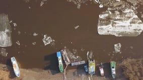 Alguns barcos no banco de rio quando a tração do gelo no tempo de mola video estoque