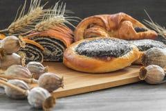 Alguns bolo e strudel da semente de papoila em uma placa de madeira Imagem de Stock Royalty Free