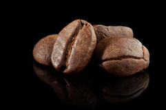 Alguns feijões de café no preto Fotografia de Stock Royalty Free