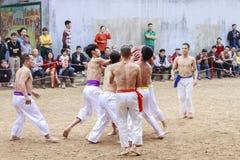 Alguns homens novos jogam com a bola de madeira no ano novo lunar do festival em Hanoi, Vietname o 27 de janeiro de 2016 Imagens de Stock Royalty Free
