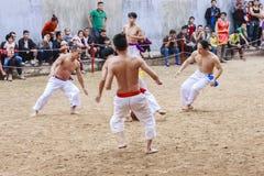 Alguns homens novos jogam com a bola de madeira no ano novo lunar do festival em Hanoi, Vietname o 27 de janeiro de 2016 Fotografia de Stock Royalty Free