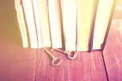 Alguns livros com chaves do estilo antigo em uma tabela de madeira Imagens de Stock Royalty Free