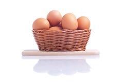 Alguns ovos marrons em uma cesta em uma placa de corte pequena isolada sobre Fotografia de Stock Royalty Free