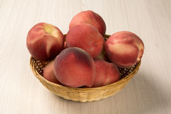 Alguns pêssegos em uma cesta sobre uma superfície de madeira Foto de Stock Royalty Free