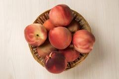 Alguns pêssegos em uma cesta sobre uma superfície de madeira Imagem de Stock Royalty Free