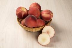 Alguns pêssegos em uma cesta sobre uma superfície de madeira Fotografia de Stock