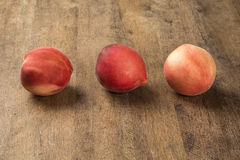Alguns pêssegos em uma cesta sobre uma superfície de madeira Imagens de Stock Royalty Free
