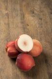 Alguns pêssegos em uma cesta sobre uma superfície de madeira Imagens de Stock