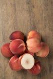Alguns pêssegos em uma cesta sobre uma superfície de madeira Fotografia de Stock Royalty Free