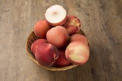 Alguns pêssegos em uma cesta sobre uma superfície de madeira Fotos de Stock Royalty Free