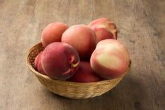 Alguns pêssegos em uma cesta sobre uma superfície de madeira Imagem de Stock