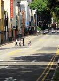 Alguns povos estão cruzando a estrada reta Imagem de Stock Royalty Free