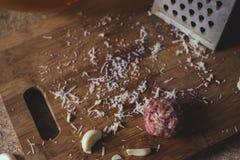 Alguns queijo, carne e alho em uma tábua de pão de madeira fotografia de stock